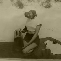 Image of Woman on beach blanket with radio