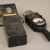 Image of A-C Volt Ammeter - A-C Volt Ammeter, black Bakelite case with meter at center front with glass cover, case is paddle shape with narrow hand grip at bottom top has silver colored metal clamp mechanism, range selector slide switch located above hand grip and below meter, two terminal screw post connectors located on front at either side of meter face, with leather carrying case.