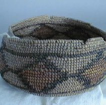 Image of Basket - Coiled mission basket made of rush and root. Has sewn on band of red-brown diamonds with black borders.