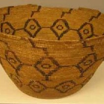 Image of Basket - Coiled basket, tall bowl shape, light tan overall coloration with two bands of dark brown stylized geometric diamond shaped decorations.