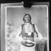 Image of Alexandro (Big Jim).  Black and white card photograph depicting a standing Native American man holding a pistol.  Copy of an earlier photograph. Maker's Mark: Rinehart Quantity: 1 Card photograph - Photograph