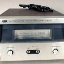 Image of 8-track tape player - Walnut case with silver metal and black plastic front.  2 knobs and 2 plug-ins for microphones.  Black cord.