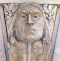 Image of Keystone - A wedge-shaped keystone of a portrait of a male, Native American face. The head is facing forward; mouth closed; slightly furrowed brow; eyes w/out pupils gazing forward; the hair is parted down the middle, shoulder length, away from the face below the cheekbones and banded 2/3 of the way down; drapes slightly over the crest of the serpentine scroll upon which the head rests; the head is flanked by olive branches w/leaves and berries on either side. The subject appears to be middle aged. Location: Colorado Springs Pioneers Museum Facade