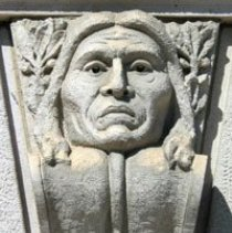 Image of Keystone - A wedge-shaped keystone of a portrait of a male, Native American face. The head is facing forward; mouth is closed and appears to be frowning; deep lines around nose and mouth; lines in forehead; hollowed cheeks; eyes w/pupils are gazing forward; hair is parted down the middle, shoulder length and slightly draping over the crest of the serpentine scroll upon which the head rests. The head is flanked on either side by olive branches w/leaves and berries. The subject appears to be middle aged. Location: Colorado Springs Pioneers Museum Facade