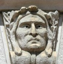 Image of Keystone - A wedge-shaped keystone of a portrait of a male, Native American face. The head is facing forward; mouth closed; full face w/out lines; eyes w/out pupils gazing slightly to the PL; hair is shoulder length, parted down the middle, and slightly draping over the crest of the serpentine scroll upon which the head rests. The top of the head is crowned by a stylized head dress that drapes forward. The head is flanked on either side by olive branches w/leaves and berries. Location: Colorado Springs Pioneers Museum Facade