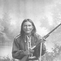 Image of Al-Chi-Say, Apache.  Black and white photographic print depicting a seated Native American male holding a rifle. Maker's Mark: Baker & Johnston - Photographs