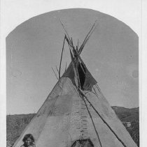 Image of Assinnaboine Indian Lodge.  Black and white card photograph depicting two women and three children sitting in front of a teepee.  Copy of a c. 1878 photograph. Maker's Mark: W. E. Hook - Photographs