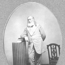 Image of Albert Pike.  Black and white photographic print, mounted.  Reproduction of an earlier photograph.  Full length portrait.  Depicts Albert Pike wearing a Masonic collar and leaning against a pillar with book on top. Maker's Mark: Unknown - Photographs