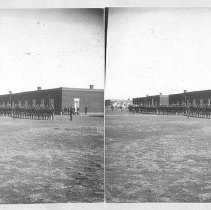 Image of Battalion Inspection, Fort Union, New Mexico.  Black and white photographic stereograph depicting soldiers in formation in front of buildings. Maker's Mark: Unknown - Stereograph