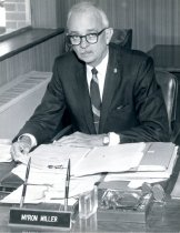 Image of Mr. Myron Miller seated at school office desk, c. 1968