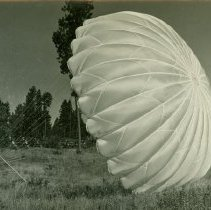 Image of Smokejumper on the Ground Holding Lines of Inflated Parachute