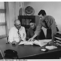Image of 3 men at desk looking at documents.  504546 - 2004.075.069