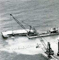 Image of Water-borne cranes remove rock from barges and place on breakwater