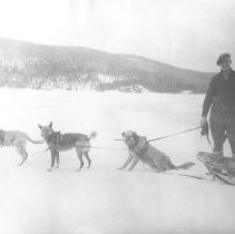 "Image of 3 - Deputy Chief Ranger, J.R. ""Jack"" Boyle on the lake with a dog team in front of Kish Kaduk Lodge, Cedar Lake."