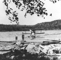 Image of 103 - Three men from the New York fishing party on Lake Opeongo stand in the water in front of a plane.