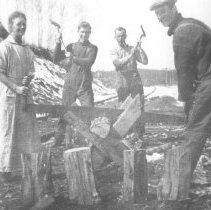 "Image of 117 - Mrs. Edwin Thomas, Billy White, Walter ""Chum"" Worsely and Edwin Thomas behind Canoe Lake station chopping wood."