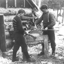 Image of 304 - Sharpening axes in the logging camp.