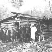 Image of 307 - Men posing outside a round log building.