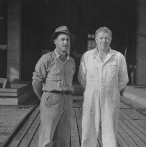 Image of Harold Haines and Red McCrae standing in front of the Hangar at Smoke Lake.
