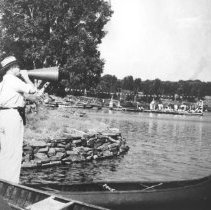 Image of Alymer Blackburn calling off for the Cache Lake Regatta in front of the Highland Inn.