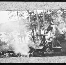 Image of 1913 - Elliot Law cooking on canoe trip.