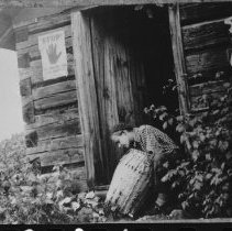 Image of 1538 - Esther Keyser in doorway of Ranger Cabin on Misty Lake.