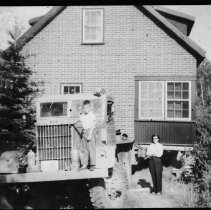 Image of 4099 - Mrs. Harold Hanes, and son Peter, Standing Beside a House as it is Being Moved
