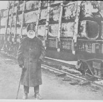 Image of 4133 - J.R. Booth Standing Beside a Load of Waney Timber