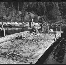 Image of 4177 - Using a Backhoe to Unload the Logs From Nominigan Lodge