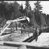 Image of 4179 - Using a Backhoe to Unload the Logs From Nominigan Lodge