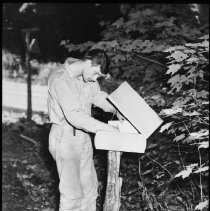 Image of 5183 - Unidentified person signing the visitor register on the Deer Lake Trail.