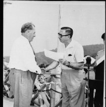 Image of 5529 - Mr. Andrew M. Grant is presented with the ' Order of the Chieftains of Algonquin ' by the Hon. Kelso Roberts, Q.C., Minister of Lands & Forests, Lake of Two Rivers, July 11, 1964.
