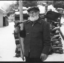 """Image of 5683 - Henry Taylor, holding a shovel and an axe over his shoulder like a """"chickadee"""", Bancroft, 1979."""