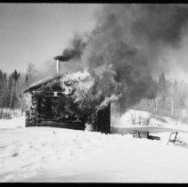 Image of 5798 - Burning the ranger cabin at Shad Lake, March 19 1962.