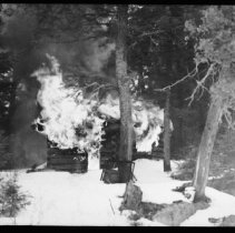 Image of 5799 - Burning the ranger cabin at Cinderella Lake, March 20 1962.