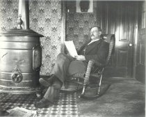 Image of Unidentified man in rocking chair indoors