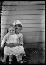 Image of Glass negative of two children seated outdoors, ca. 1910 - Children