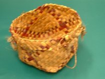 Image of Kete - A five sided, cube type flax woven basket, of brown flax colour, maroon and purple. Two thin, twisted fibre handles at the side.   tassels where the thin handles end on the side of the kete.