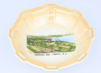 "Image of Dish - Small circular porcelain dish with raised sides. Coloured picture labeled Caroline Bay, Timaru, N.Z. on interior. Top of sides has 8 regularly spaced rectangular flanges jutting out slightly, with horizontal gash on each. Interior of dish with pink/tan glaze with changing intensity, exterior white. Base with maker's transfer mark, small crown with ""Victoria China Czechoslovakia"" beneath."