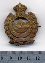 """Image of Badge, Military - A brass military badge, shaped with a crown at the top, leaves around the outer edge, and within the inner circle is (faintly) men in a canoe with mountain behind. Enscribed on the badge is """"26th Reinforcements, New Zealand"""". Has a clip on the reverse side."""