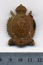 "Image of Badge, Military - An oval brass military badge, shaped with a crown at the top, leaves around the outer edge and crossed rifles behind, and within the inner circle it reads ""26th Reinforcements, N.Z.E.F."" and on scroll across the bottom "" AKE AKE KIA KAHA"""