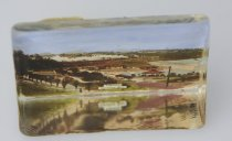 Image of Paperweight - Triangular glass paperweight with colour tinted black and white photograph of the band rotunda and the Bay hall at Caroline Bay at the back.  Behind the buildings a steam train is travelling north.