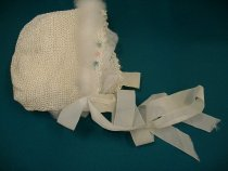 Image of Bonnet, Infant - Infants bonnet crocheted in ivory silk thread and with a swansdown trim around the edge.  There are pink and blue flowers embroidered on between the swansdown and the picot edge of the bonnet near the face.  The bonnet has a long ribbon at each side for tying in a bow under the chin.