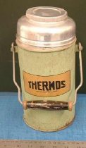 """Image of Thermos - Green aluminium thermos has gold coloured label with """"Thermos registered trade mark"""" in black. Has aluminium tin screw on lid which opens to reveal cork inner lid and then the glass interior. Near the top there is a square shaped handle made from thick wire which is not removable and with a black wooden hand grip.  On the base is """"Thermos registered trade mark"""".  Sits inside Basket 2001/060.093 H10/07, SR1"""