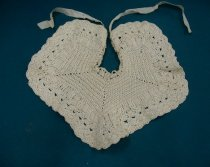 Baby's bib crocheted from cream silk.Bib is shaped...