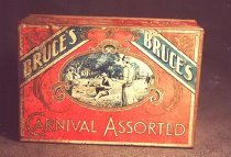 "Image of Tin, Biscuit - Red rectangular Bruce's biscuit tin with tight-fitting, separate lid.  Lid and tin are red with gold edges.  Lid has an oval with an illustration of a picnic scene featuring a family in 1920s clothing.  Around the oval are scroll designs and in each corner at the top a diagonal blue ribbon that reads ""Bruce's"". Underneath the oval is ""Carnival Assorted"".  Sides of tin read ""Carnival Assorted"" and ends read ""Bruce's."" All lettering is silver."
