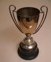 "Image of Trophy - Trophy cup  with thin double handle each side and black plastic base.  Engraved on the front of the cup is ""Ray Bennett Challenge Cup"" and the back is dates and names of the winners (1985-1999)"