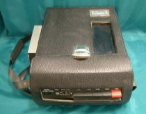 "Image of Camera, Motion-picture - Akai video camera in case with separate recording unit.  Camera  is hand held and has cream plastic cover with black cylindrical  handle projecting down from the body.  Eye viewer at the back and lens with large round removable black cap with ""Akai"" at the  front.  Above the lens is a small microphone projecting out from  the body.  Trigger style on /off button below the lens.  Thick  black electric cord projects from the rear of the camera with  connection to the other unit?