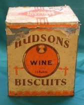"Image of Tin, Biscuit - Square biscuit tin for Hudsons biscuits.  The top and front are covered with cream coloured paper. There are 4 red lines form ""+"" with  red diamond shaped in centre ""Hudsons Biscuits"".  ""CPCP W"" hand printed in purple ink in top right corner.  The front centre has a red circle with wheat sheaf in a small brown circle at the top, and ears of wheat along the sides.  A red ribbon and bow out comes from each side near the bottom of the circle.  ""Hudsons Biscuits Wine 13 Packets"".  The lid is hinged at the back and opens upward.  ""3/-"" in a circle is stamped into the bottom of the tin."