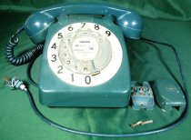 """Image of Telephone - Dark green bakelite telephone with a black base that sits on table. The face of the phone has a round cream bakelite ring with the numbers """"0"""" to """"9"""" printed in black. Inside this is a thin metal disc also with the numbers """"0"""" to """"9"""" printed in black, covered by clear plastic. A thicker clear plastic disc on top with holes corresponding to where the numbers are for dialing the required digits of the telephone number. A small piece of metal stops the finger from dialing each digit too far around. A paper label in the centre, printed with """"Timaru"""", """"Tu - """", """"Std Code 056"""" and """"Emergency 111"""", typed beside the """"Tu"""" is """" 80 358"""". Handwritten in pen is """"from 11-30pm Fri 24-8-90"""", """"68"""" added before the telephone number and the """"056"""" crossed out and replaced with """"03"""".  The handset of ear and mouth piece sits across the top of the telephone and is connected to the phone by dark green cord.  There is also a dark green cord at the back of the phone to connect to the outside wires. On the base is white stamp that is difficult to read """"Made In England By [.............] Electric Co Ltd Of England"""". Also on base is sticker which reads """"NZPO Wkshp Timaru"""", """"Overhauled/Repaired"""", """"By 40. Date 24/2/823"""", """"Test By......,  / / """", """"Engr 26"""". Four round rubber feet on the base for sitting on the table.  In a separate bag is what could be a phone jack for attaching to the wall and three screws."""